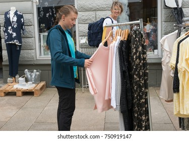 girl with her mother makes shopping looking at clothes