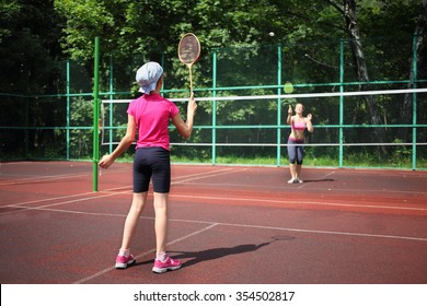 Girl with her mother play tennis on the tennis court, view from the back