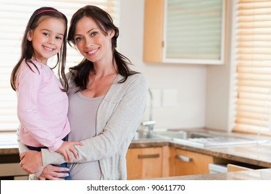 Girl and her mother posing in a kitchen