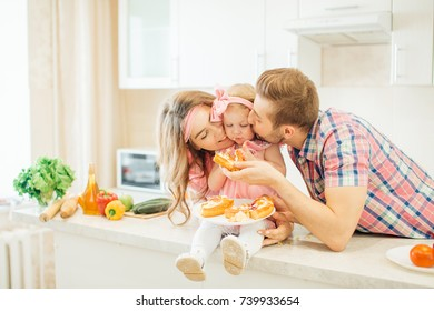 girl and her parents are eating vegetables and smiling while cooking in kitchen.