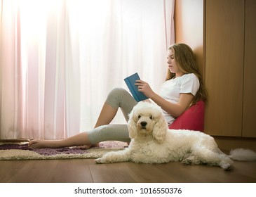 Girl in her room with a dog reads a book