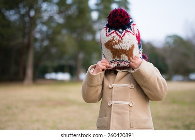 Girl hide her face with knit hat