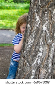 the girl hides behind a tree