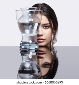 Girl hides her face behind a glass vase with water. Beauty portrait of young woman at the mirror table. Female on gray background.