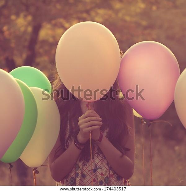 Girl hiding behind the balloon