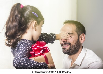 Girl hiding gift while covering happy father eyes at Father day