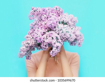 Girl hiding head bouquet lilac flowers over colorful blue background