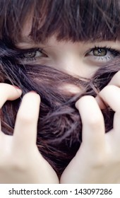 Girl hiding with her hair looking at camera