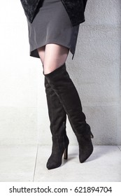 girl in high black boots, a coat in the office. lookbook, women's high leather boots