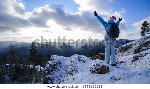 A girl high in the mountains rejoices at the sunrise, raising her hands up. The view from the back. Winter, forest and rocks, snow. Sun rays through the clouds.