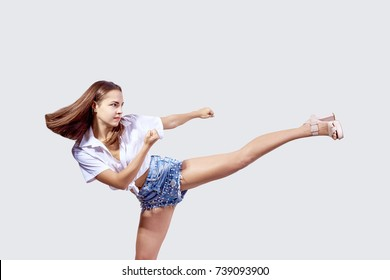 A girl in high-heeled shoes makes a high kick