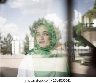 Girl with hijab on window