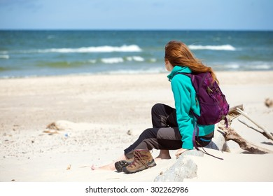 girl  hiker with a backpack sitting on the beach and looking at sea, Baltic Sea