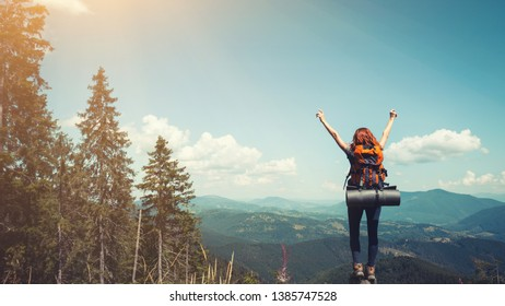 girl hiker with a backpack standing on the background of mountains and forests. Carpathians, Ukrainian landscape.