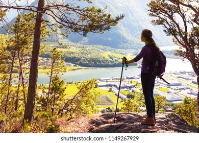girl hiker with a backpack and trekking pole sitting and looking on Romsdalsfjorden and Andalsnes, Norway