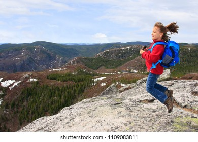 Girl hiker jumping and admiring the beauty landscape from the summit of  summit of Mont du Lac-des-Cygnes in Parc national des Grands-Jardins, Quebec, Canada