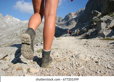 girl hiker with mountain shoes climbing up a long trail, over rocks