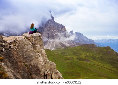 girl hiker sitting at the edge of rock. Dolomites, Italy.