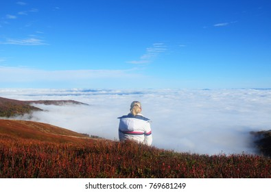 Girl hiker sitting on the rock mountain , relaxing and inspiring  on the top of the himalayan mountain. Meditation nature.