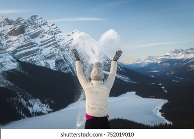Girl hiker spreading snow in heart shape at Bow Summit. View over Peyto Lake, Banff, Canadian Rockies, Alberta, Canada. Cold freezing winter activities. Outdoor lifestyle happiness concept.
