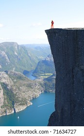 girl hiker standing on Preikestolen and looking at the mountains. Preikestolen -famous cliff at the norwegian mountains