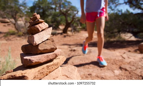 A girl hikes nearby a cairn on a desert trail in the Colorado National Monument near Fruita, Colorado.
