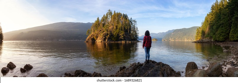 Girl Hiking in the Canadian Landscape during a vibrant winter sunset. Hike on Jug Island Trail in Belcarra, Vancouver, British Columbia, Canada. Nature Panorama Background