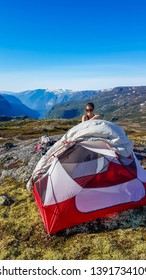 A girl in hiking outfit puts a tent up. She is camping in the wilderness. The backdrop is Eidfjord and tall glacier. Adventurous solo traveling girl. Bright and sunny day. Perfect day for a hike.