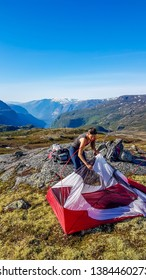 A girl in hiking outfit struggles to out the tent up together. She is camping in the wilderness. The backdrop is Eidfjord and tall glacier. Adventurous solo traveling girl. Bright and sunny day