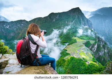 Girl with hiking rucksack sitting on the edge of the rock and taking amazing photos of breathtaking Machupicchu mountains landscape