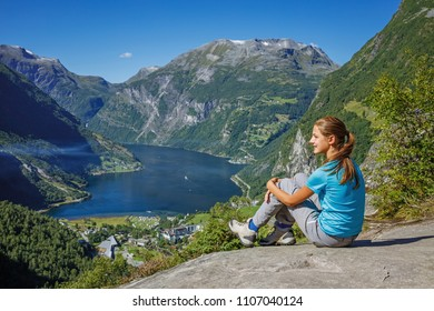 Girl hiking to Seven Sisters Waterfall in Geirangerfjord. Geiranger, Norway.