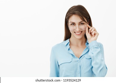Girl is hinting adventures waiting for us. Portrait of curious flirty attractive woman, taking off glasses and touching rim, smiling broadly, having intriguing idea or plan, feeling joyful and playful