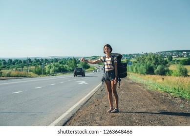 Girl hitchhiking. Backpacker on road