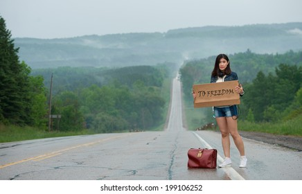 girl hitchhiking holds up a  sign