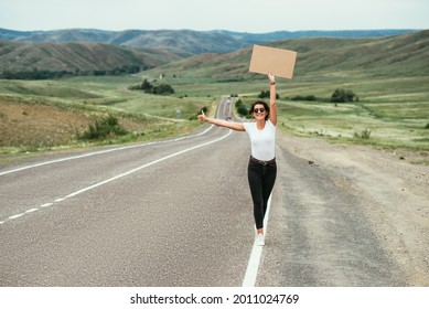 The girl is hitchhiking. A woman is hitchhiking on the road. Hitchhiking with a raised thumb on a rural road. The concept of travel and hitchhiking. Beautiful girl traveler. Copy space