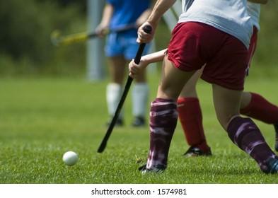 A girl hits a field hockey ball