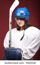 a girl hockey player in uniform posing with helmets off in front of red