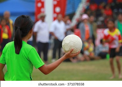 girl hold a ball on her hand during handball game in student sport
