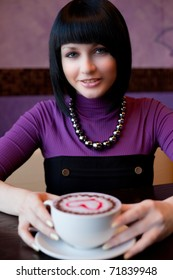 girl hold cup of coffee in hand and smiling