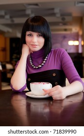 girl hold cup of coffee in hand looking straight