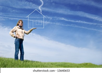 Girl hold dreaming house in the field