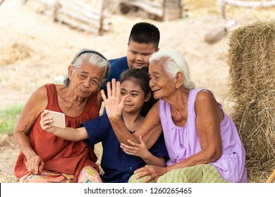 Girl hold hand phone in hand talk to miss somebody and selfie together with her family, boy and grandmother. Technology connect motion. all feel happy.