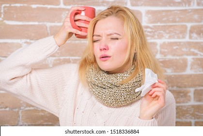 Girl hold tea mug and tissue. Runny nose and other symptoms of cold. Drinking plenty fluid important for ensuring speedy recovery from cold. Drink more liquid get rid of cold. Cold and flu remedies.