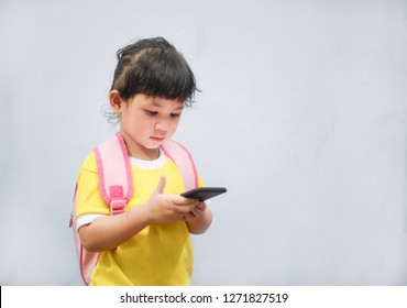 Girl hold telephone in hand and playing smartphone watching cartoons at the school / Asia child 2-3 year old Kids addicted to games problems of children use smartphone technology