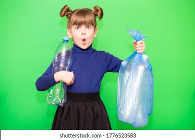 Girl hold trash bag and plastic bottle and shows interest in environmental issues isolated on green background. Child accustomed to bear responsibility. Plastic trash sorting concept