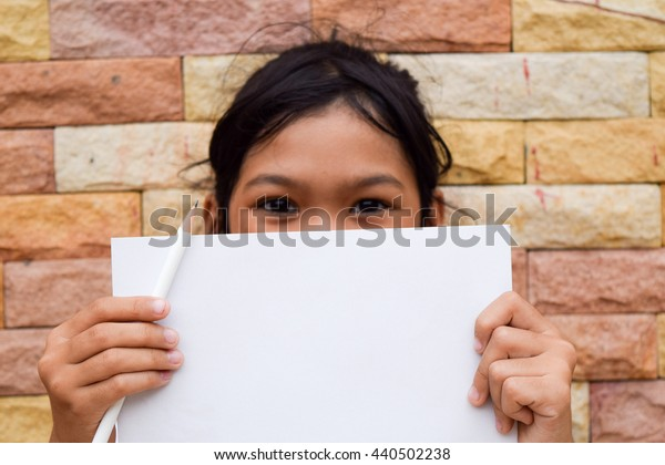 girl hold white blank paper on stone wall