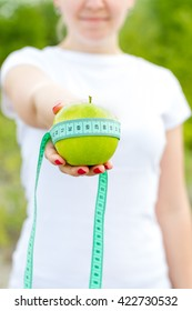 Girl holding an apple and tape measure in hand.