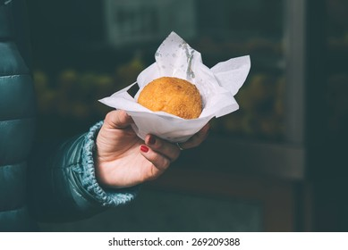Girl holding arancino, traditional street food from Sicliy. Toned image