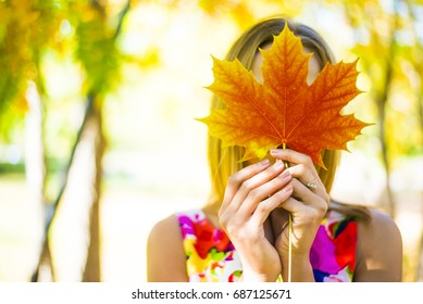 girl holding autumn green maple leaf on the background colorful autumn forest, park. blond woman closed face with maple leaf in hand, autumn park with sunshine. closed eyes. relax