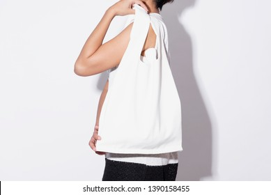 Girl is holding bag canvas fabric for mockup blank template isolated on gray background.  global warming concept.